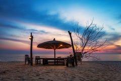 Holzstühle und Regenschirme auf Sandstrand Stockfotografie