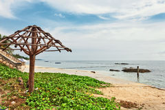 Holzstühle und Regenschirme auf weißem Sandstrand lizenzfreie stockfotos