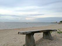 Holzstuhl auf sandigem Strand vor dem Meer Lizenzfreie Stockfotografie