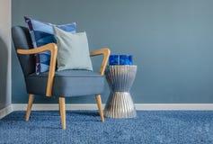 Holzstuhl mit blauem Farbkissen auf Teppich Stockbild