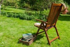 Holzstuhlbücher und -hut im Garten stockfotografie