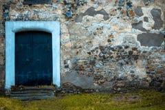 Holztür in der alten steinigen Wand Stockbild