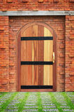 Holztür mit alter Backsteinmauer und Steinboden Lizenzfreie Stockbilder