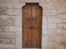 Holztür mit Metallgriff, Steinwand Stockfoto