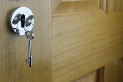 Holztür mit Schlüssel in Verschluss G stockbilder