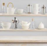 Holztisch über Hintergrund von Regalen mit Küchengeräten stockfotografie
