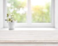 Holztisch auf defocused Sommerfenster mit Blumentopfhintergrund stockfoto