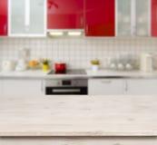 Holztisch auf rotem modernem Küchenbank-Innenraumhintergrund Stockfotos