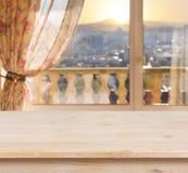 Holztisch auf unscharfem Balkonfensterhintergrund Stockbild