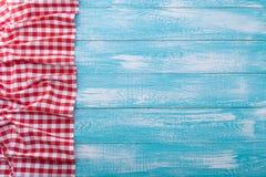 Holztisch bedeckt mit kariertem Rot des Tischdeckenstoffes Stockfoto