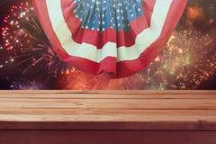 Holztisch über Feuerwerken des Juli-Hintergrundes Straßen-Clown grüßt Leute Stockfotografie