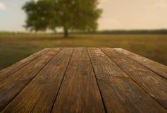 Holztisch draußen mit Herbstfeldhintergrund Stockbild