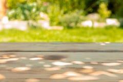 Holztisch in einem Garten an einem sonnigen Tag Stockfotos