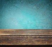 Holztisch gegen blauen strukturierten Hintergrund Lizenzfreies Stockbild