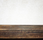 Holztisch gegen weißen Hintergrund mit Blumenmuster Stockbilder