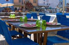 Holztisch im Freien eingestellt für Abendessen Stockfotos