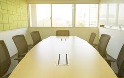 Holztisch im Konferenzzimmer mit Schalldämpfersonnenlicht vom Fenster Lizenzfreie Stockbilder