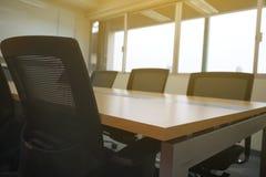Holztisch im Sonnenlicht des weißen Brettes des Konferenzzimmers vom Fenster Stockfoto