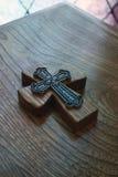 Holztisch mit angehobenem Kreuz in der Mitte Stockbilder