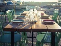 Holztisch mit grünem Stuhlrestaurant im offenen Raum auf dem Hintergrund des Liegeplatzes mit Yachten Übertragung lizenzfreie stockfotos