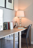 Holztisch mit Lampe und Büchern im modernen Funktionsrauminnenraum Stockfoto