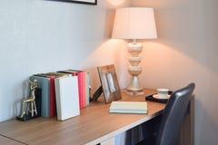 Holztisch mit Leselampe und Büchern im Funktionsraum Stockbild