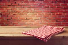 Holztisch mit Rot überprüfter Tischdecke über Backsteinmauer Stockbilder