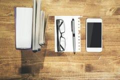 Holztisch mit Smartphone und Buch Lizenzfreie Stockbilder