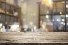 Holztisch mit Unschärfehintergrund der Kaffeestube Stockfotos