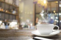 Holztisch mit Unschärfehintergrund der Kaffeestube Lizenzfreie Stockfotografie