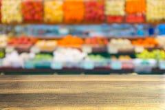 Holztisch mit unscharfem Hintergrund von Früchten Stockfotos