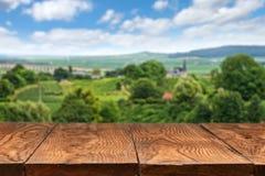 Holztisch mit Weinberglandschaft Stockfotografie