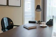 Holztisch und Bücher im modernen Funktionsraum Lizenzfreie Stockfotos