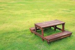 Holztisch und Stühle eingestellt auf grünen Rasen im Garten lizenzfreie stockfotos