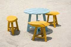 Holztisch und Stühle eingestellt auf Strandsand Lizenzfreies Stockbild