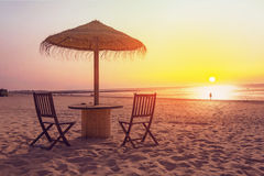 Holztisch und Stühle mit Regenschirm auf dem Strand Lizenzfreies Stockfoto