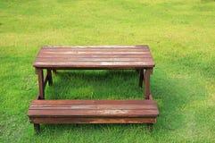 Holztisch und St?hle eingestellt auf gr?nen Rasen im Garten lizenzfreies stockbild