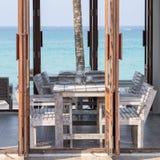 Holztisch und Stühle im kleinen tropischen Café auf blauem See- und Himmelhintergrund Lizenzfreies Stockbild