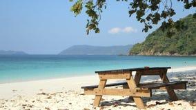 Holztisch unter dem Baum auf dem Strand Stockbild