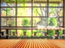 Holztisch vor unscharfem Kaffeestubehintergrund lizenzfreie stockfotografie