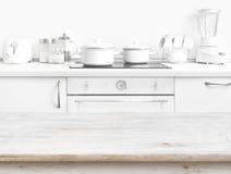 Holztisch vor unscharfem weißem Küchenbankinnenraum Lizenzfreies Stockfoto