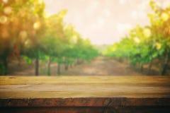 Holztisch vor unscharfer Weinberglandschaft Stockbild