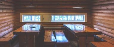 Holztische und Bänke in einem Blockhaus Lizenzfreie Stockfotos