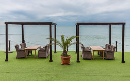 Holztische und geflochtene Stühle, die Meer und Himmel übersehen palme Stockfoto