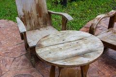 Holztische und Stühle auf Fliesenböden im Garten stockfotos