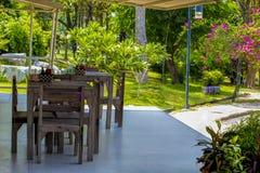 Holztische und Stühle im Garten Stockfotografie
