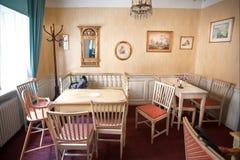 Holztische und Stühle ohne Besucher im klassischen Innencafé innerhalb des alten Hauses Lizenzfreie Stockfotografie