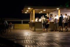 Holztischspitze über abstraktem Unschärfehintergrund des Leuteabendessens Restaurant am im Freien lizenzfreie stockbilder