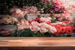 Holztischspitze/Theke vor unscharfem Blumenspeicher lizenzfreie stockbilder