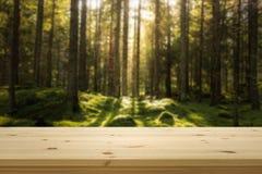 Holztischspitze vor grünem blured Wald für Produktanzeigenmontage lizenzfreies stockfoto
